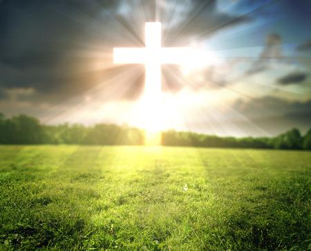 Een helder gloeiend kruis over een grasveld