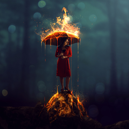 A woman with a burning umbrella in a dark forest