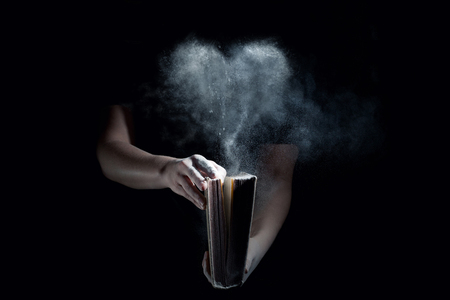 An old book is opened up and the dust forms a heart shape