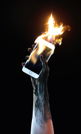 Hand holding a burning cell phone