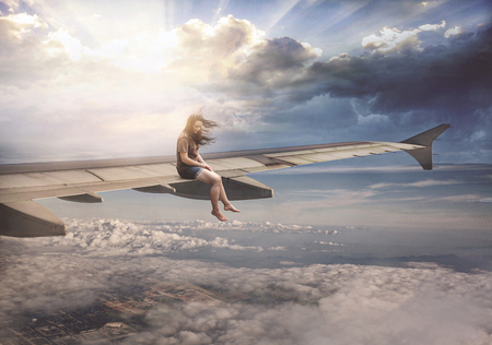 A woman sits casually on a plane wing high in the sky