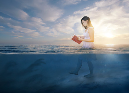 A woman reads her Bible as she walks into deep waters