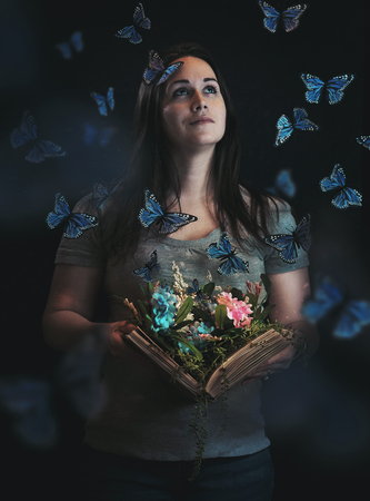 A woman holds an open book and a beautiful garden and butterflies come out