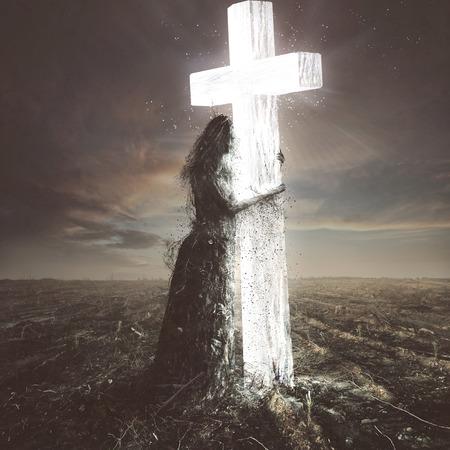 Una mujer hecha de palos y tierra se aferra a la cruz resplandeciente Foto de archivo