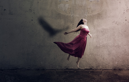 A woman jumps up and her shadow is an eagle Stock Photo