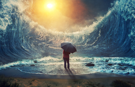 A woman surrounded by large waves and holding an umbrella.