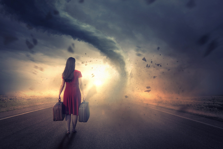 Woman walks towards a tornado and bright sunset