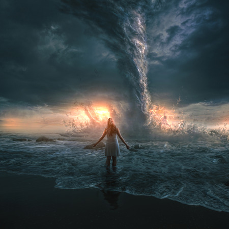 A woman bravely stands in front of a large tornado over the ocean.