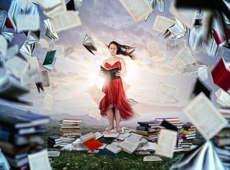 A woman reads her Bible with other books flying around