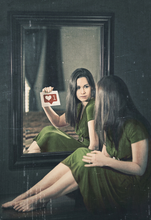 A woman looking into a mirror and wanting approval. Stock fotó