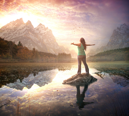 A woman stands in awe and worship during a beautiful sunrise Stok Fotoğraf