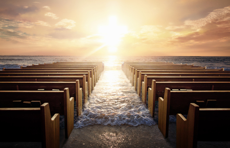 Several church pews at the beach during sunrise