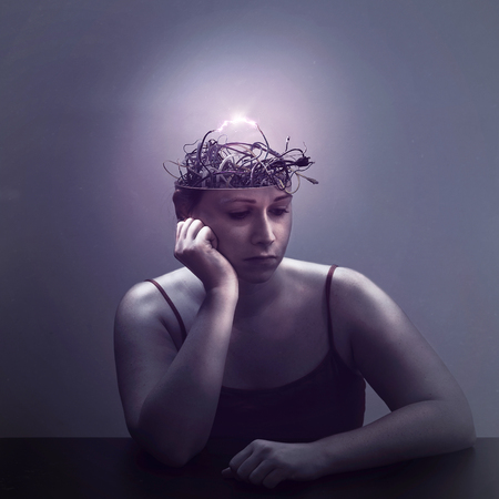 A woman lost in thought as her mind is filled with electric wires Фото со стока