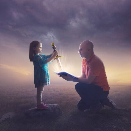 A little girl pulls a bright sword out of the Bible.
