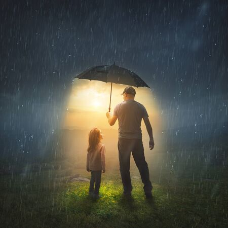 A father holds up an umbrella to protect his child from the rain.