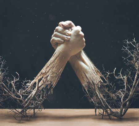 Two hands are holding together while twigs and braches are coming from the arms. Фото со стока