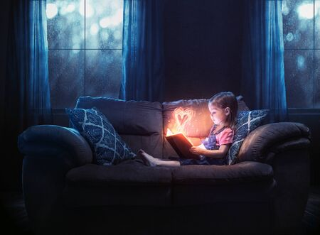 A little girl reading alone with a color heart glowing out of the pages Фото со стока
