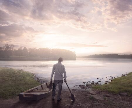 A man prepares to go on a lake at sunrise Фото со стока