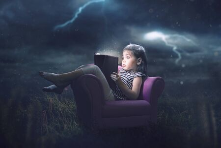 A little girl is scared and reading during a storm Фото со стока