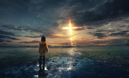 A little girl stands in the rain with a glowing cross in the sky