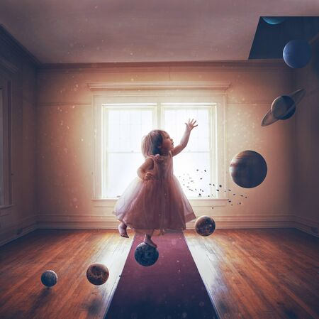 A little girl steps on the planets of the solar system