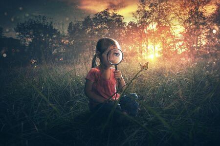 A little girl watches butterflies in a field