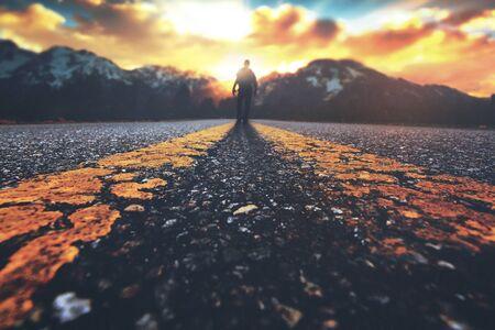 A man walking down a road towards a mountain sunset Фото со стока