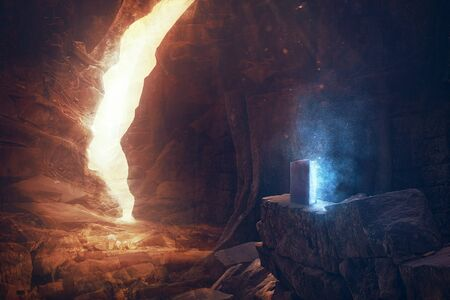 An open Bible buried deep in a cave with colorful lights and dust Фото со стока