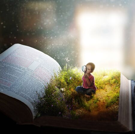 A little girl watches butterflies on the pages of an open Bible