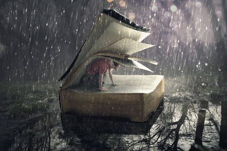 A man finds safety under the pages during a rain storm.