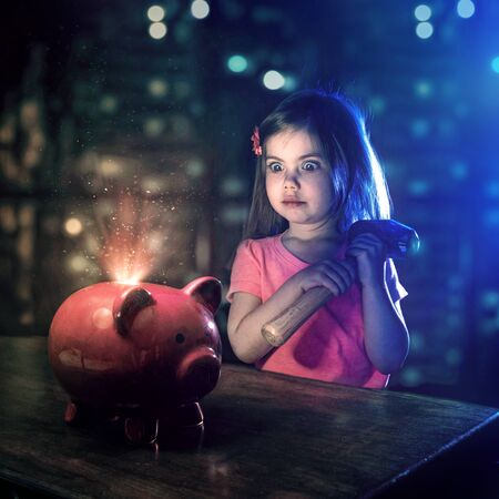 A little girl looks at her piggy bank with a hammer in hand