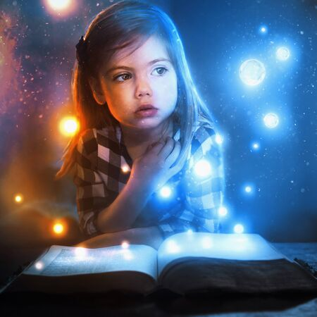 A little girl watches glowing lights and stars flow out of an open book. Фото со стока