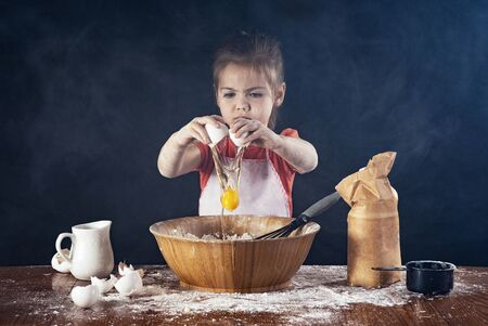 A little girl breaks an egg into a large bowl in the kitchen and makes a mess.