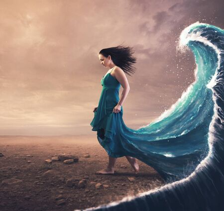 A woman with a blue dress and large wave behind her. Фото со стока
