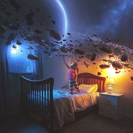A little girl uses her imagination in her bedroom to see the rings of Saturn