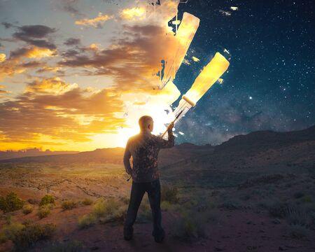 A man paints a beautiful sunrise over a night sky.