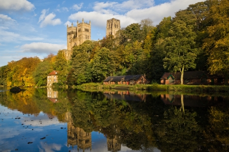 Durham Cathedral above the Old Fulling mill and boat houses reflected in the river wear in autumn colours