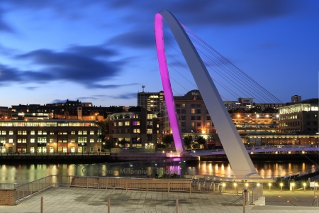 Night view of the Newcastle and Gateshead quaysides linked by the Millennium bridge lit in a pink light. Editorial