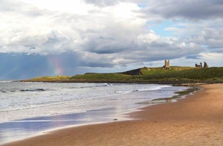Dunstanburgh Castle and rainbow viewed from the beach in Northumberland,England, between the villages of Craster and Embleton