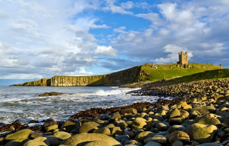 Dunstanburgh Castle viewed from the rocky shore in Northumberland,England, between the villages of Craster and Embleton