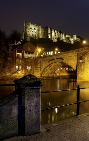 Durham Castle lit by spotlights at night viewed from the river Wear.
