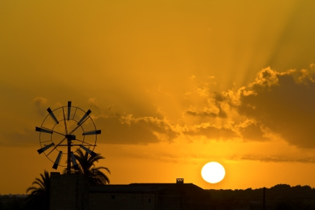 Sunset on the island of Mallorca, the sun setting behind one of the may windmills on the island  Stock fotó