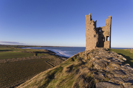 Dunstanburgh Castle lies on a spectacular headland on the coast of Northumberland in northern England