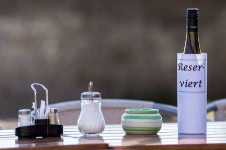 reserved sign: Reserved sign on restaurant table with empty dishes and glasses