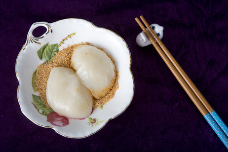 Hakka Mochi with peanut powder and wooden chopsticks on a black background Stock fotó