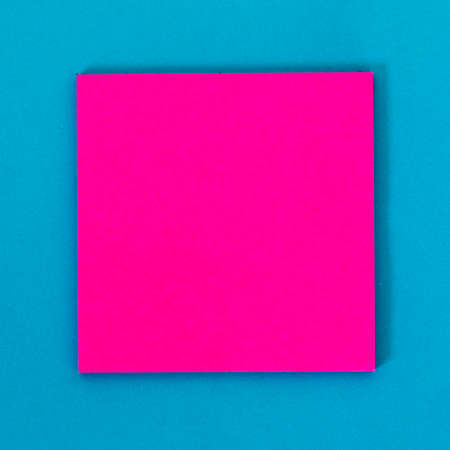 Pink empty note paper, blue background. Stock Photo