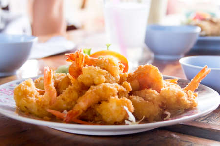 Fried prawn balls on a wooden table, backgrounded with bowls and cups