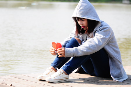 mujer triste: femenino triste con el corazón de papel rojo Foto de archivo