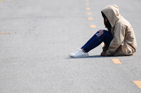 dolorous: Lonely Girl Sitting on the Road Stock Photo