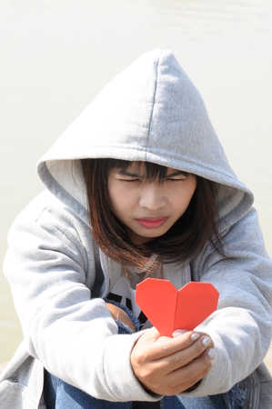 to confess love: Sad Girl Looking to Red Heart on Hands